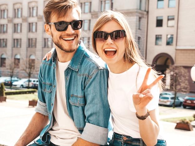Портрет улыбается красивая девушка и ее красивый парень. женщина в повседневной джинсовой одежде. . показывает знак мира Бесплатные Фотографии
