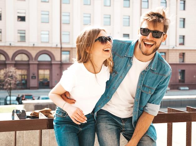 笑顔の美しい少女とカジュアルな夏服とサングラスで彼女のハンサムなボーイフレンドの肖像画。 。ハグ 無料写真