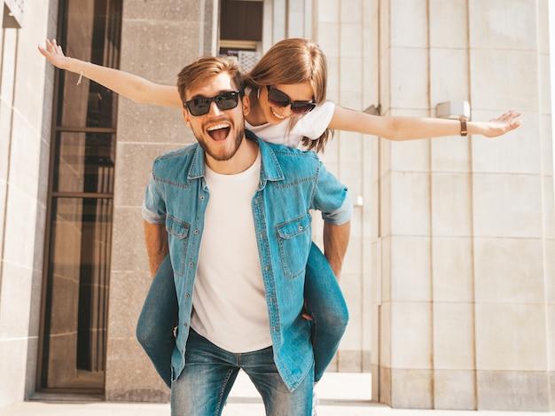 カジュアルな夏服で笑顔の美しい少女と彼女のハンサムなボーイフレンド。彼のガールフレンドを背負って彼女の手を上げる男。 無料写真