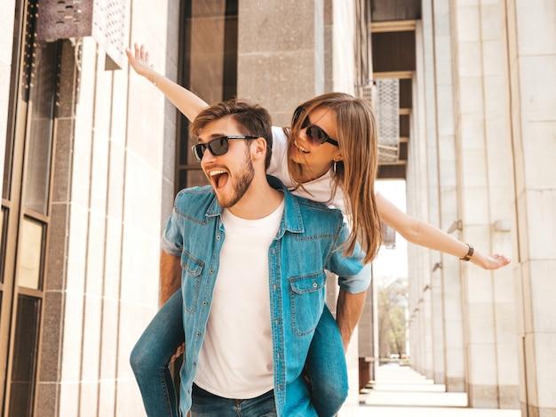 Улыбка красивая девушка и ее красивый парень в повседневной летней одежде. мужчина несет свою подругу на спине и она поднимает руки. Бесплатные Фотографии
