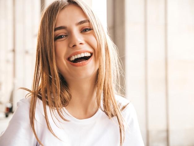 夏の流行に敏感な服に身を包んだ美しい笑顔金髪モデルの肖像画。 無料写真