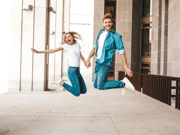 Портрет улыбается красивая девушка и ее красивый парень в повседневной летней одежды. счастливая веселая семья прыгает и веселятся на улице фоне. схожу с ума Бесплатные Фотографии