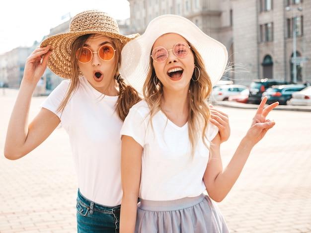 Две молодые красивые белокурые улыбающиеся хипстерские девочки в модной летней белой футболке одеваются. сексуально шокированные женщины позируют на улице. удивленные модели с удовольствием в солнцезащитных очках и шляпе. показывает знак мира Бесплатные Фотографии