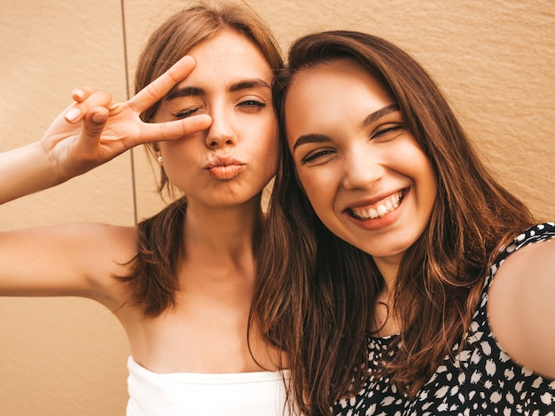 Две молодые улыбающиеся женщины битник в летней одежде. Бесплатные Фотографии