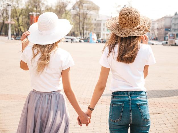Назад двух молодых красивых белокурых улыбающихся хипстерских девочек в модной летней белой одежде футболки и шляпе. , пара, держась за руки Бесплатные Фотографии