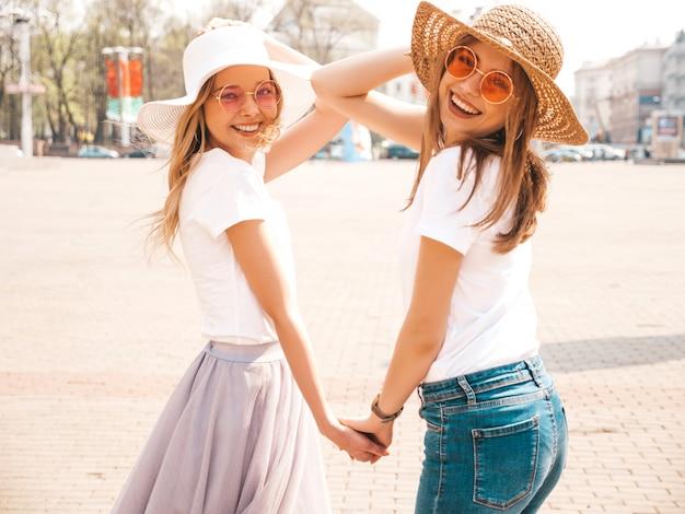 Портрет двух молодых красивых белокурых улыбающихся хипстерских девочек в модной летней белой футболке одевается. , позитивные модели, держа друг друга за руки Бесплатные Фотографии