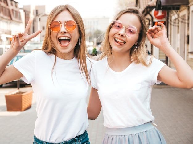 Портрет двух молодых красивых белокурых улыбающихся хипстерских девочек в модной летней белой футболке одевается. , позитивные модели с удовольствием. показывает знак мира Бесплатные Фотографии