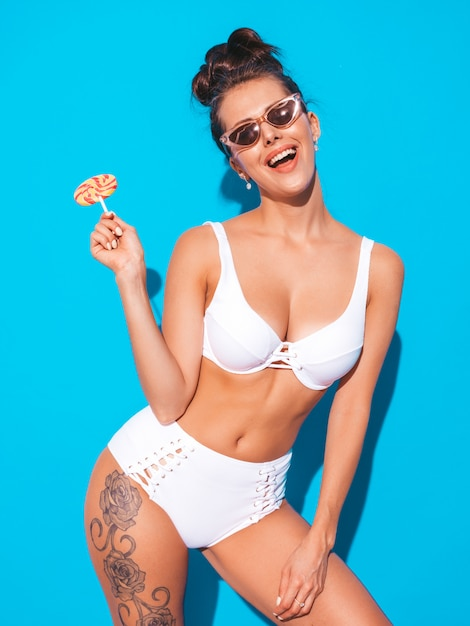 グールの髪型と若い美しいセクシーな笑顔の女性。カジュアルな夏の白い水着でトレンディな女の子。青に分離されたホットモデル。食べる、キャンディロリポップをかむ 無料写真