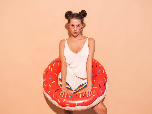 サングラスの若い美しいセクシーな笑みを浮かべて流行に敏感な女性。ドーナツリロインフレータブルマットレス付き。 無料写真