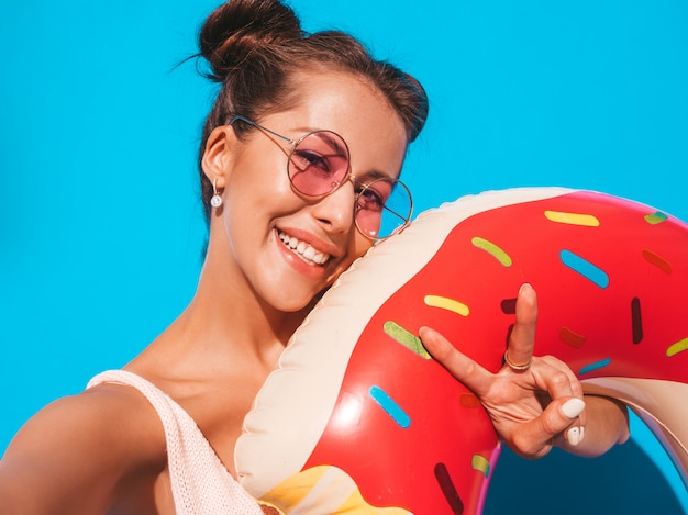 Молодая красивая сексуальная улыбается женщина битник в солнцезащитные очки. с пончиком лило надувной матрас. сходит с ума. Бесплатные Фотографии