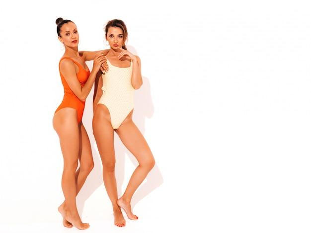 Две красивые сексуальные улыбающиеся женщины в летних разноцветных купальниках красного и желтого цвета. модные горячие модели с удовольствием. девушки изолированы. полная длина Бесплатные Фотографии