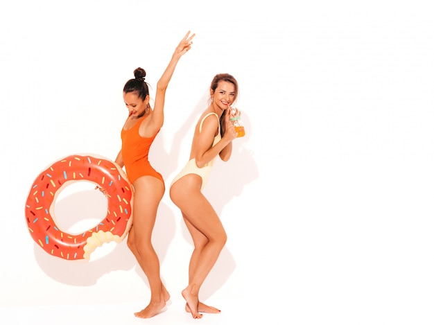 Две красивые сексуальные улыбающиеся женщины в летних разноцветных купальниках. девушки изолированы. веселые модели пьют свежий коктейль смузи напиток с надувным матрасом пончик лило Бесплатные Фотографии