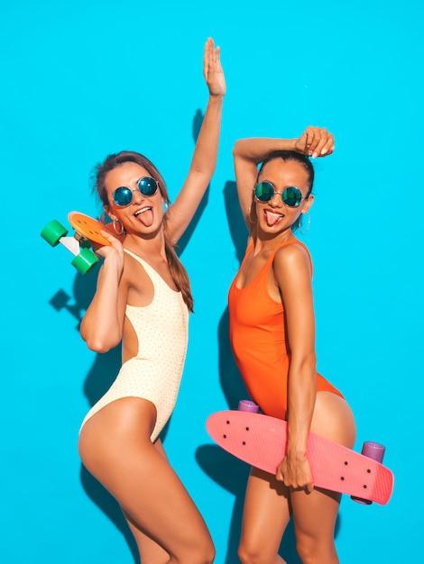 Две красивые сексуальные улыбающиеся женщины в летних разноцветных купальниках. модные девушки в солнечных очках. позитивные модели веселятся с разноцветными скейтбордами. изолированы. показывает язык Бесплатные Фотографии