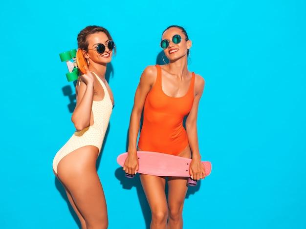 Две красивые сексуальные улыбающиеся женщины в летних разноцветных купальниках. модные девушки в солнечных очках. позитивные модели веселятся с разноцветными скейтбордами. изолированные Бесплатные Фотографии