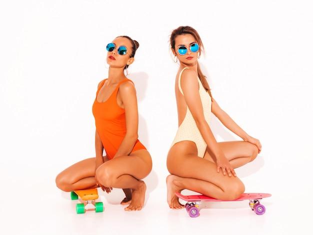 Две красивые сексуальные улыбающиеся женщины в летних разноцветных купальниках. модные девушки в солнечных очках. позитивные модели сидят на полу с разноцветными копеечными скейтбордами. изолированные Бесплатные Фотографии