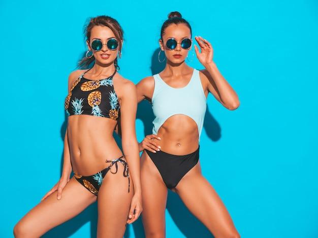 Портрет двух красивых сексуальных улыбающихся женщин в купальниках летних купальников. модные горячие модели с удовольствием. девушки в темных очках на синем фоне Бесплатные Фотографии