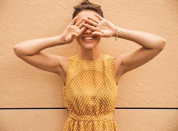 夏の黄色のドレスに身を包んだ美しい笑顔ヒップスターモデルの肖像画。トレンディな女の子が通りでポーズします。楽しくて面白い女性 無料写真