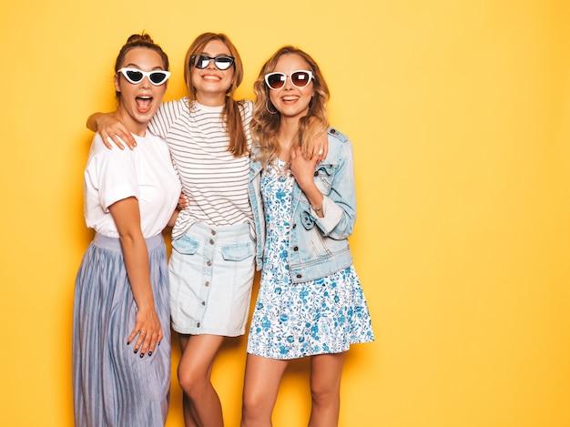 Три молодые красивые улыбающиеся битник девушки в модной летней одежде. сексуальные беззаботные женщины позируют возле желтой стены. позитивные модели веселятся в солнечных очках Бесплатные Фотографии