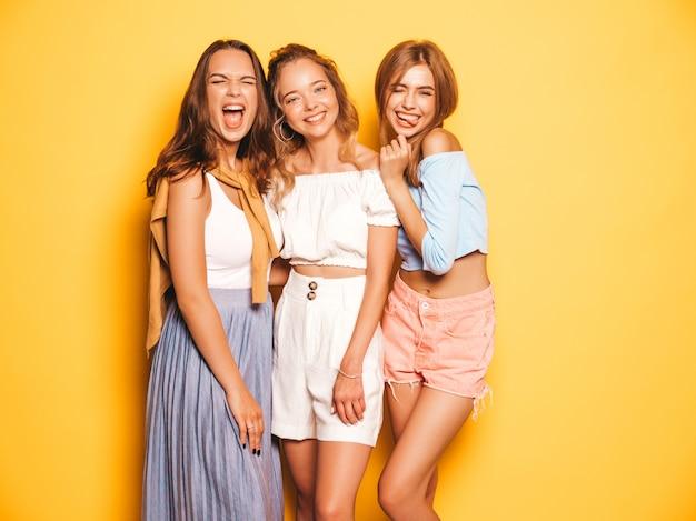 Три молодые красивые улыбающиеся битник девушки в модной летней одежде. сексуальные беззаботные женщины позируют возле желтой стены. позитивные модели сходят с ума и веселятся в солнечных очках Бесплатные Фотографии