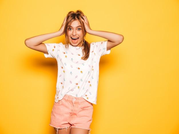 トレンディな夏のジーンズの若い美しい笑顔の内気な少女は服をショートパンツします。女性は黄色の壁に近いポーズします。ショックを受けて驚いた女性の手で頭を握りしめ、悲鳴を上げます。人間の感情 無料写真