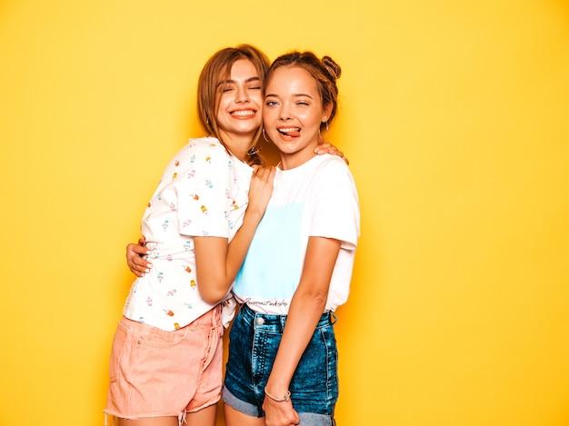 Две молодые красивые улыбающиеся битник девушки в модной летней одежде. сексуальные беззаботные женщины позируют возле желтой стены. позитивные модели сходят с ума и веселятся. Бесплатные Фотографии