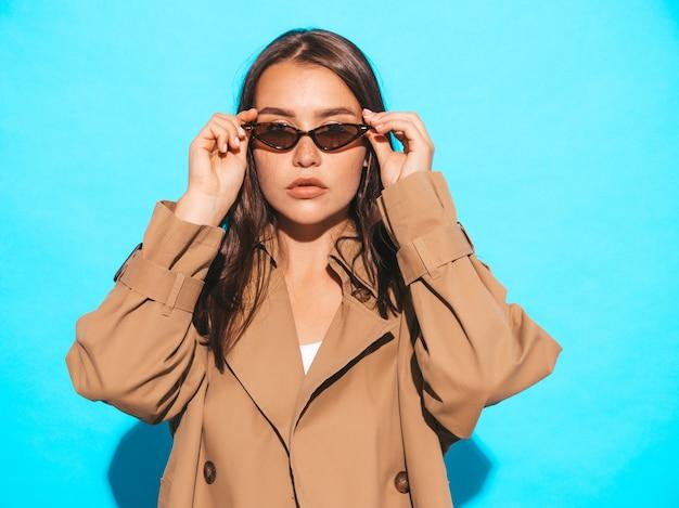 茶色のコートとサングラスで美しい白人ブルネットの女性モデルの肖像画。青い壁に近いポーズの女の子 無料写真