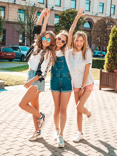 Портрет трех молодых красивых улыбающихся хипстерских девочек в модной летней одежде. сексуальные беззаботные женщины позируют на улице. позитивные модели веселятся в солнечных очках. обнимаются Бесплатные Фотографии