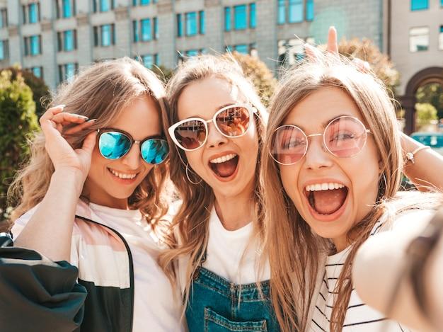 Три молодые улыбающиеся битник женщины в летней одежде. девушки, делающие фотографии автопортрета селфи на смартфоне. модели, позирующие на улице. женщина, показывающая положительные эмоции лица в солнцезащитных очках Бесплатные Фотографии