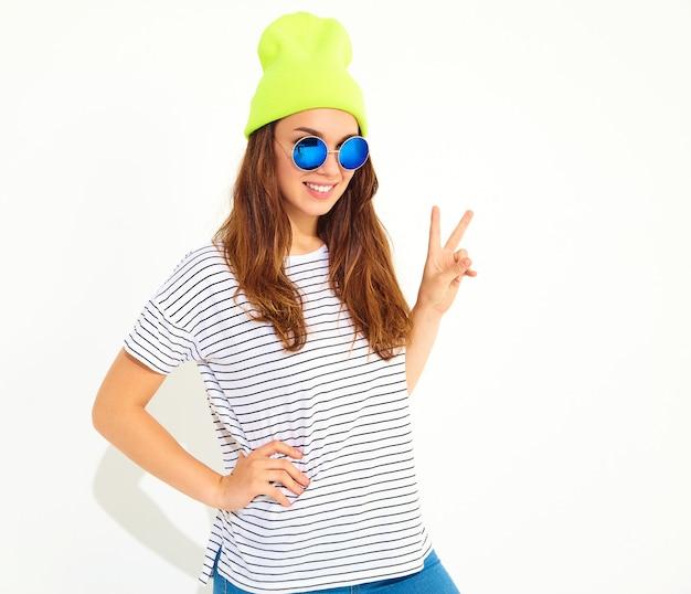 Портрет молодой стильной женской модели в повседневной летней одежде в желтой шапочке. изолированные на белом Бесплатные Фотографии