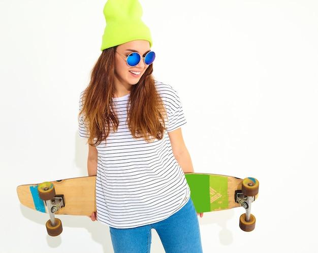 ロングボードデスクでポーズをとって黄色のビーニー帽子でカジュアルな夏服の若いスタイリッシュな女性モデルの肖像画。白で隔離 無料写真