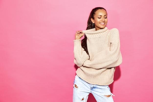 美しいセクシーな笑顔のゴージャスな女性。ピンクの壁のスタイリッシュな白いセーターで立っている女性。バレンタインデーのコンセプト 無料写真