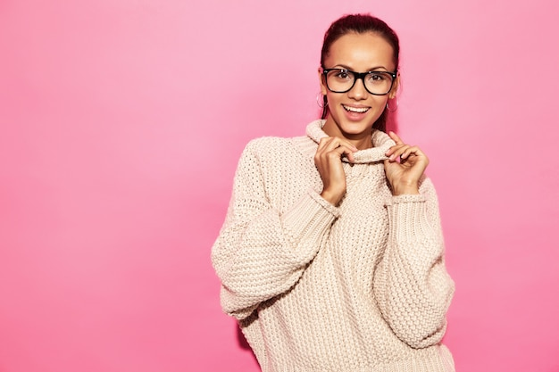 美しい笑顔のゴージャスな女性。ピンクの壁にスタイリッシュな白いセーターで立っている女性。 無料写真