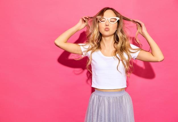 Молодая красивая женщина модные женщины в повседневной летней одежды в поддельные очки реквизит. язык тела выражение лица положительные женские эмоции. смешная модель играет со своими волосами на пи Бесплатные Фотографии