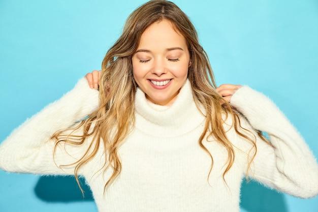 美しい笑顔金髪ゴージャスな女性の肖像画。青い壁に、スタイリッシュな白いセーターで立っている女性。冬の概念 無料写真