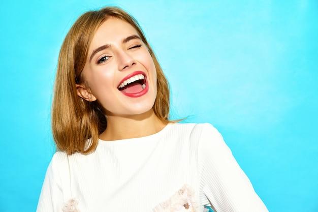 若い美しい女性。まばたきのカジュアルな夏服でトレンディな女性。青い壁に分離された面白いモデル 無料写真