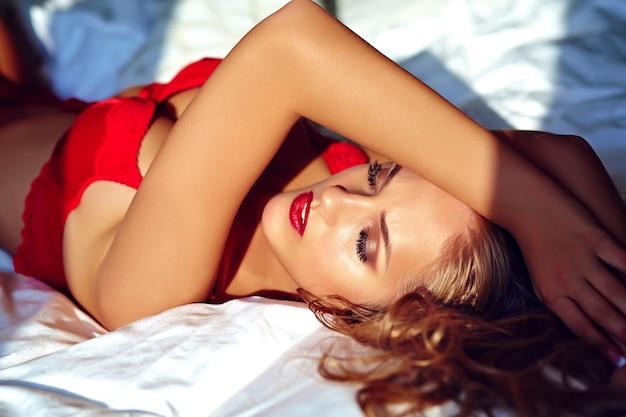 朝日の出で白いベッドに横たわっている赤のエロティックなランジェリーを着ている美しいセクシーな若い大人の金髪女性モデルのファッションポートレート 無料写真