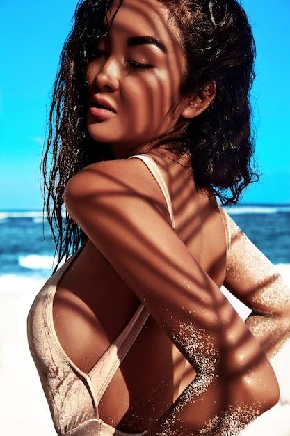 青い空と海に白い砂と夏のビーチでポーズベージュ水着で暗い長い髪の美しい白人日光浴女性モデルの肖像 無料写真