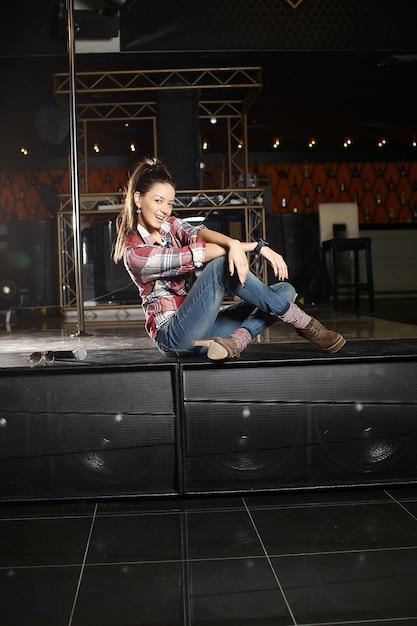 Молодая красивая улыбающаяся поп-звезда певица с микрофоном сидит на сцене в клубе Бесплатные Фотографии