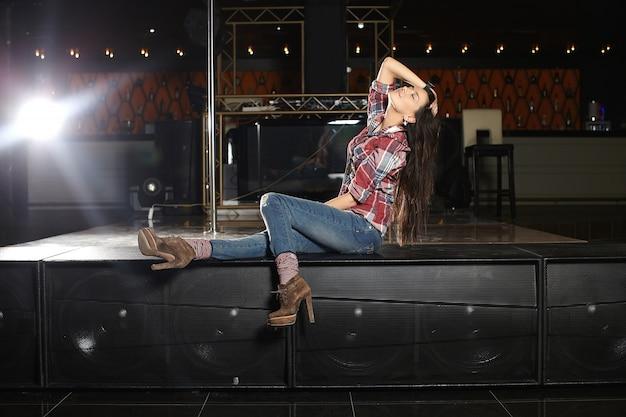 Молодая красивая поп-певица с микрофоном сидит на сцене в клубе Бесплатные Фотографии