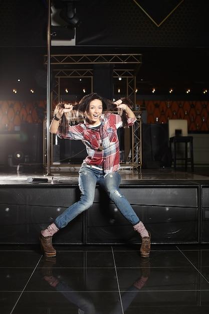 Юная красавица смешная поп-певица с микрофоном сидит на сцене в клубе Бесплатные Фотографии