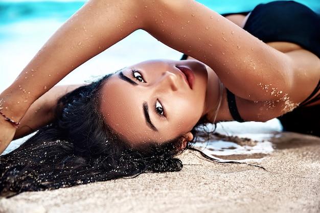 青い空と海に白い砂と夏のビーチで横になっている黒い水着で黒い長い髪と美しい白人日光浴女性モデルの肖像 無料写真