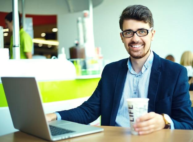 Молодой модный улыбающийся хипстерский человек, пьющий кофе в городском кафе во время обеда с ноутбуком в костюме Бесплатные Фотографии