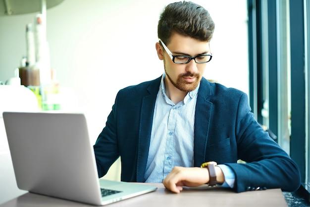 Человек битника молодой моды усмехаясь в кафе города во время обеда с тетрадью в костюме смотря часы Бесплатные Фотографии