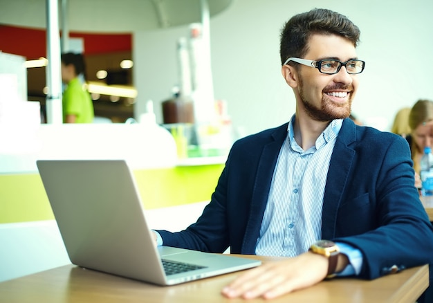Молодой модный улыбающийся битник человек в городском кафе во время обеда с ноутбуком в костюме Бесплатные Фотографии