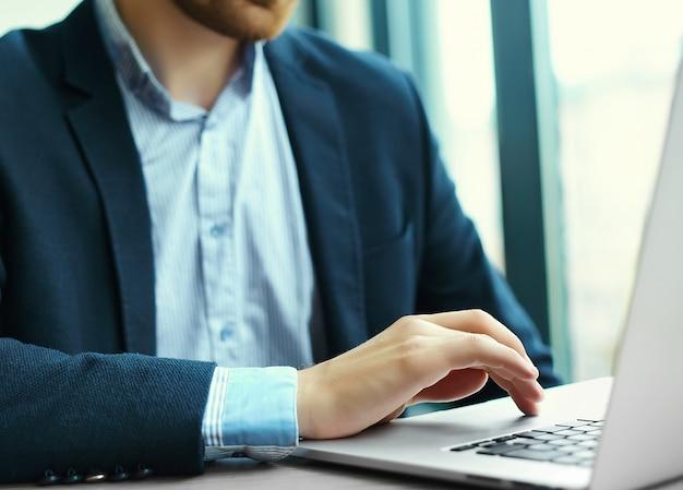 若い男がノートパソコン、ノートパソコン、職場での事業者の男の手での作業 無料写真