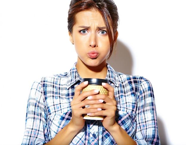 Портрет красивой стильной крутой смешной подростковой женщины с раздутыми щеками в клетчатой рубашке, держащей пластиковую кофейную чашку Бесплатные Фотографии