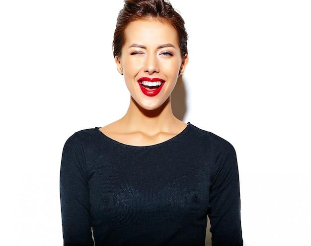 白い壁に赤い唇とカジュアルな黒い服を着て狂った陽気な笑顔ウインクファッション女性 無料写真