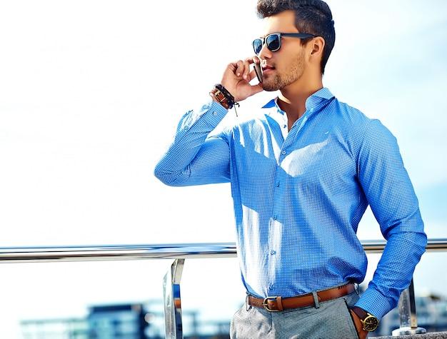 Бизнесмен в формальной одежде и солнцезащитные очки, используя свой телефон Бесплатные Фотографии