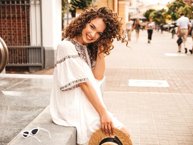 夏の流行に敏感な白いドレスに身を包んだアフロカール髪型と美しい笑顔モデル。 無料写真