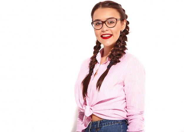 Портрет молодой счастливой улыбающейся модели женщины с ярким макияжем и красными губами с двумя косичками в летней разноцветной розовой рубашке Бесплатные Фотографии